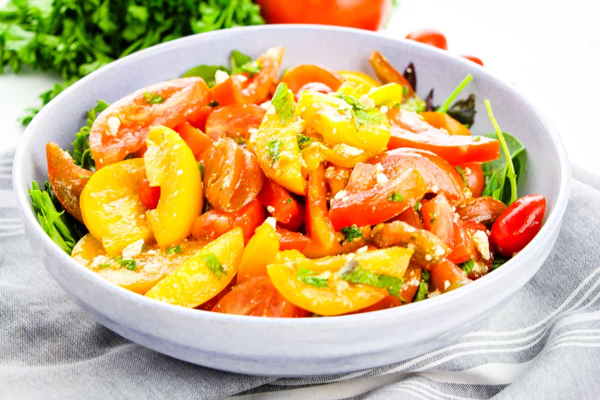 Colored tomato salad with crumbled feta and vinaigrette dressing served on bed of lettuce