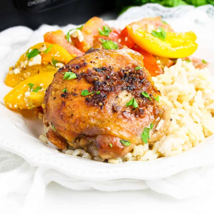 Brown sugar garlic chicken thigh made in the crockpot served over rice with tomato salad