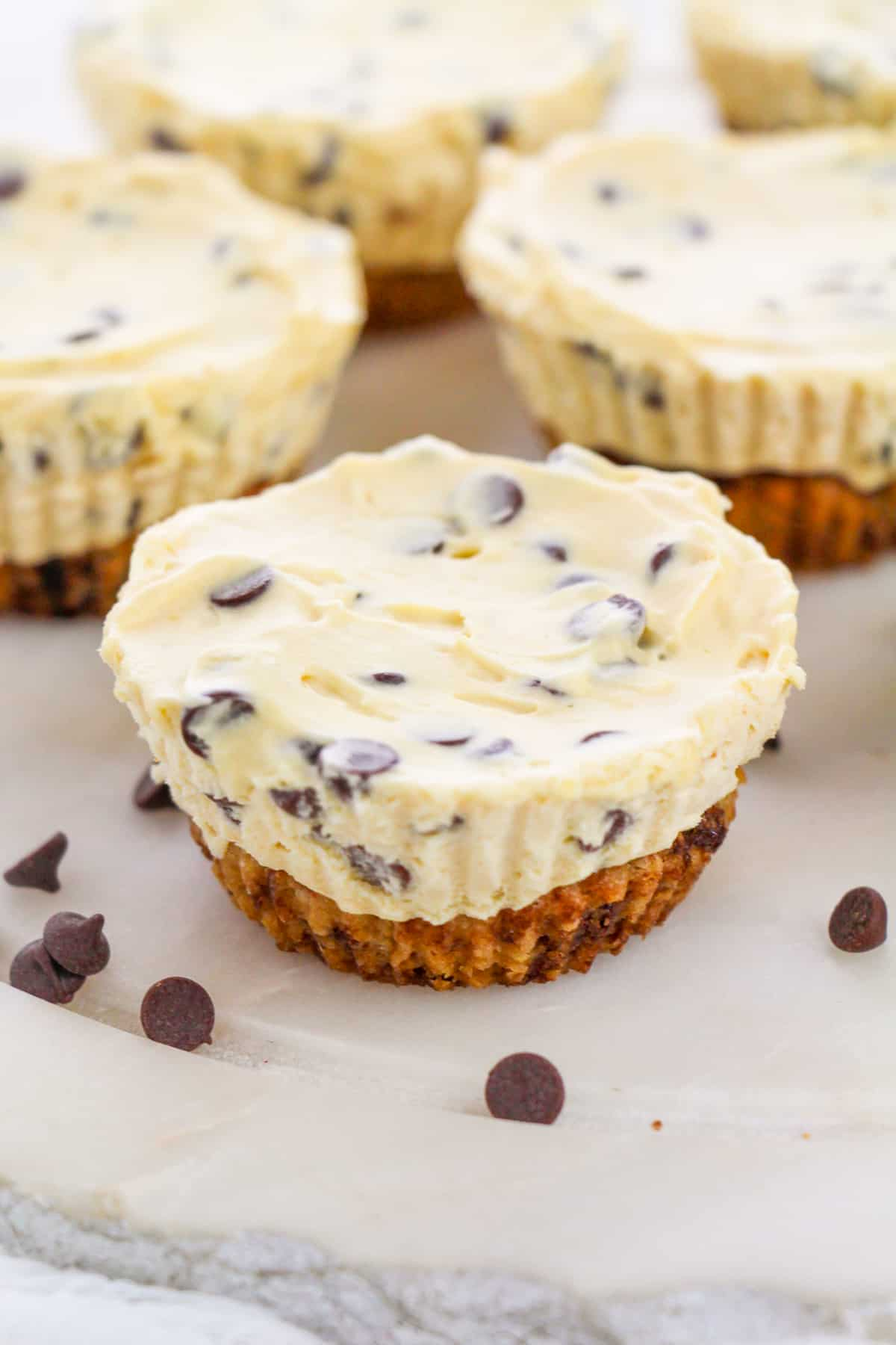 Chocolate Chip Cookie Dough Cheesecake Cups on white plate with mini chocolate chips