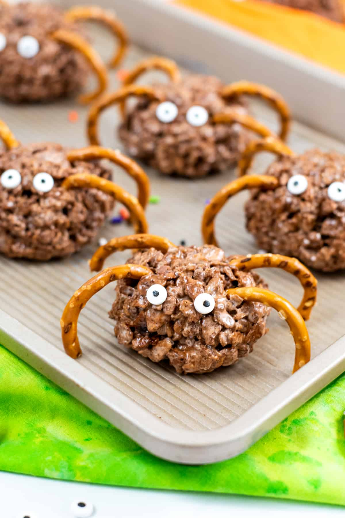 Round chocolate rice cereal treats with pretzel legs and candy eyes