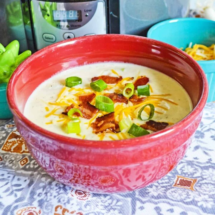 crockpot loaded baked potato soup in red bowl topped with bacon, scallions, and cheese.