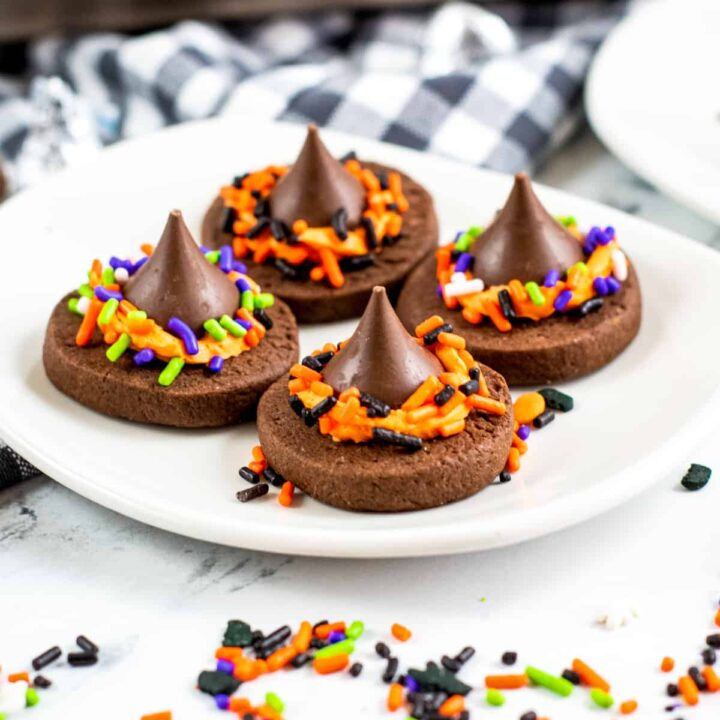 Four chocolate witch hat cookies with Hershey kisses on a white plate with halloween sprinkles around the table.