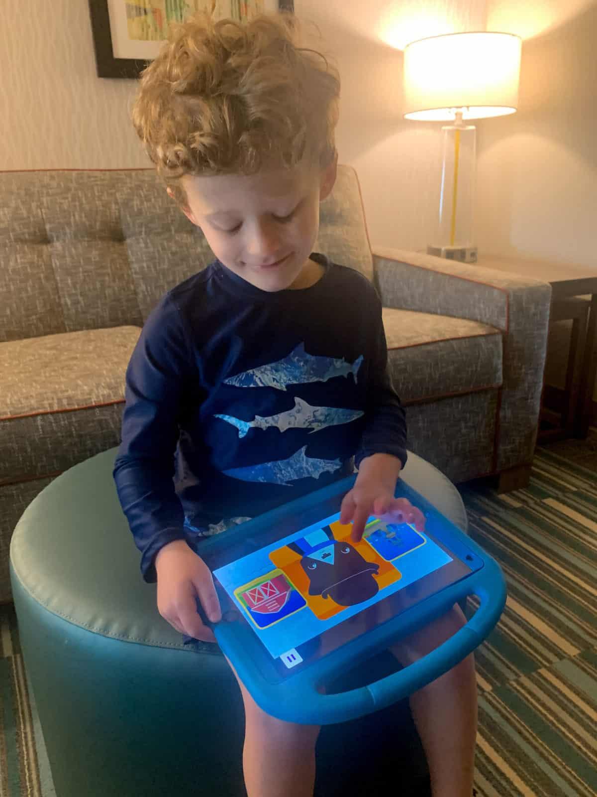 4-year-old boy interacting with Noggin app on ipad in hotel room