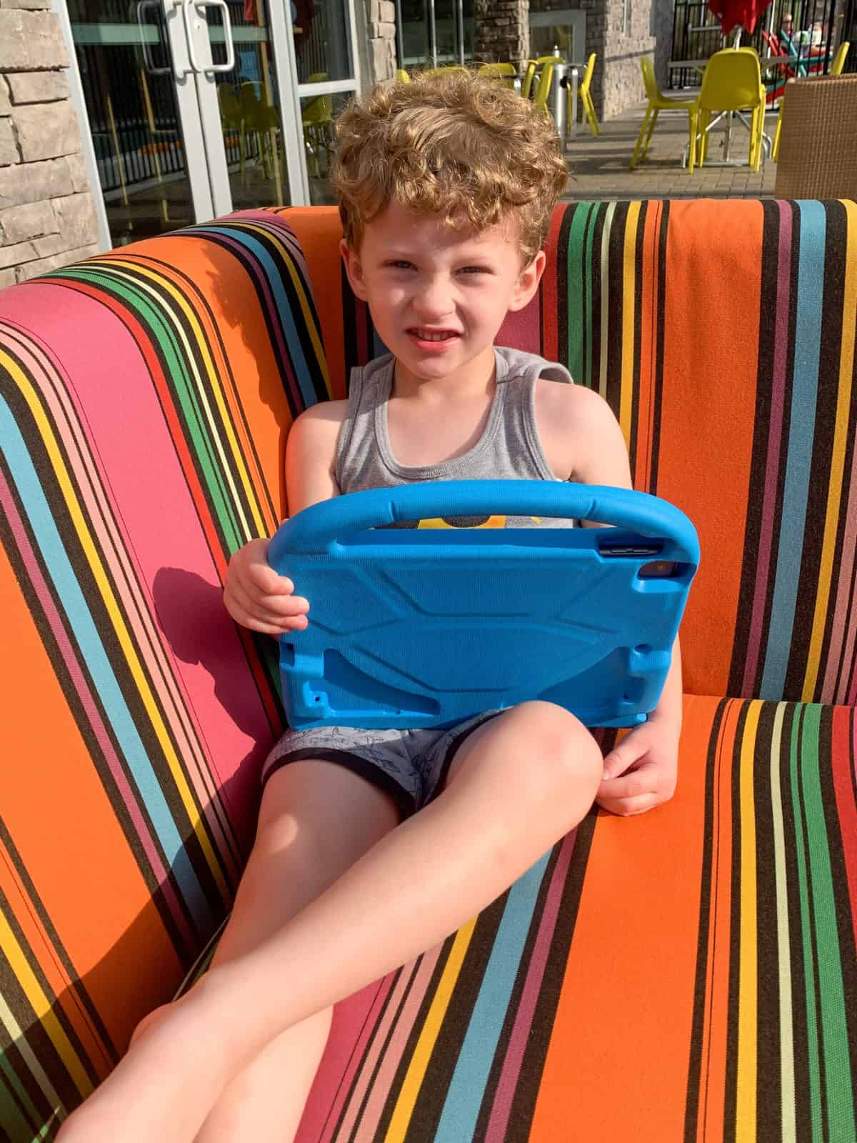 Young boy holding ipad in blue ipad case on an outdoor chair