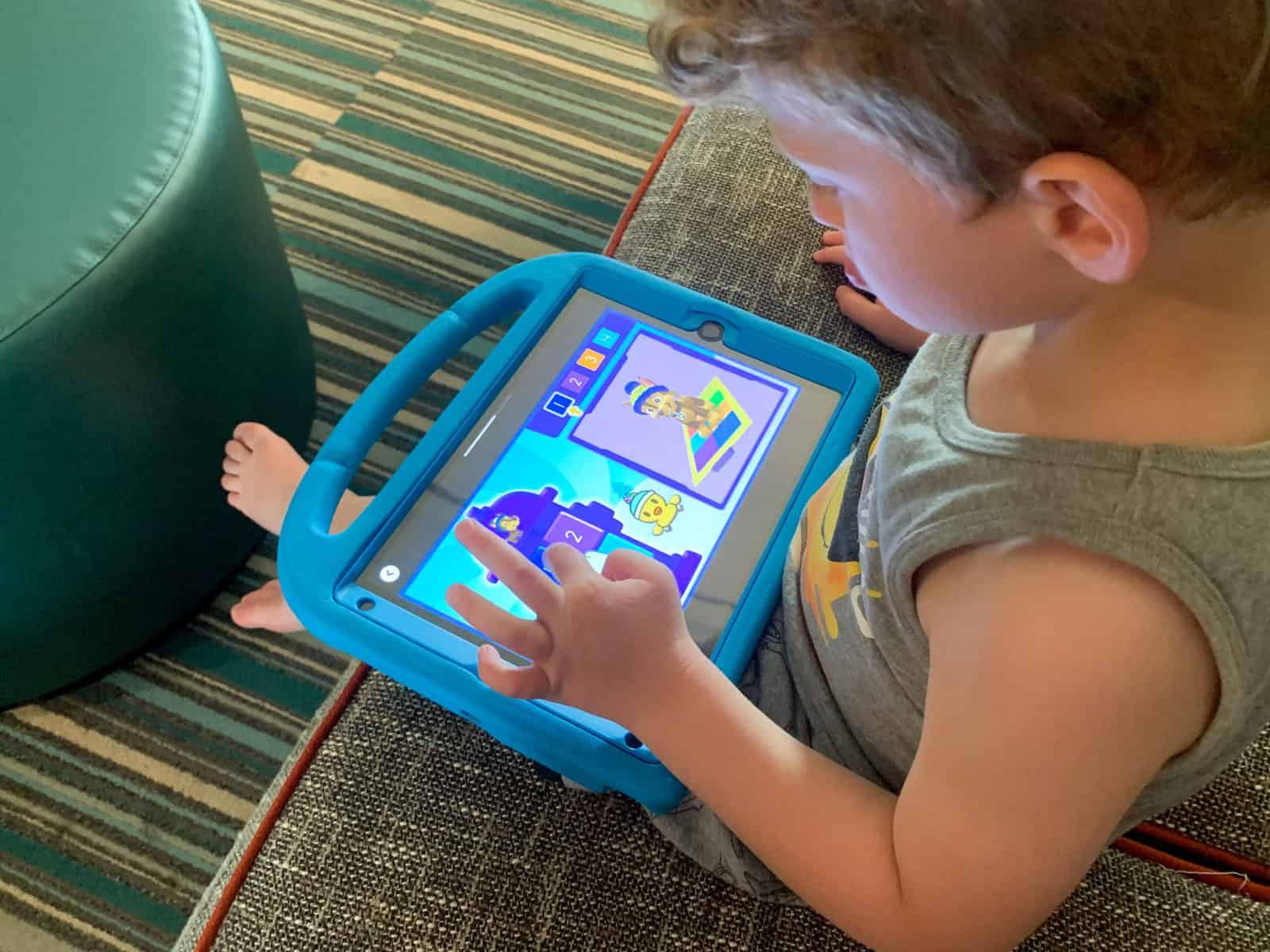 Young boy playing Noggin on ipad