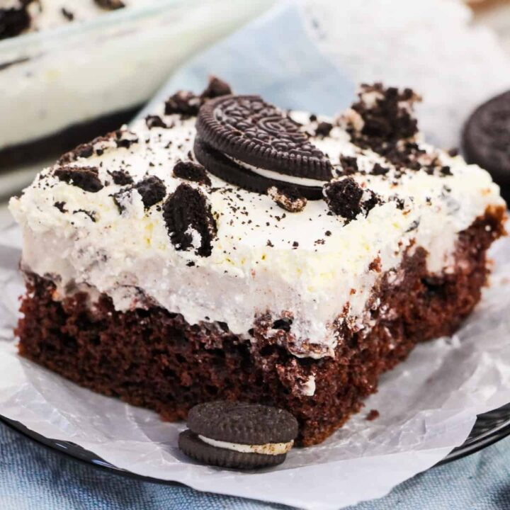 OREO Poke Cake topped with Cool Whip and pieces of OREOs