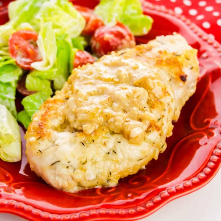 Smothered Chicken Breast served with salad on a red plate.