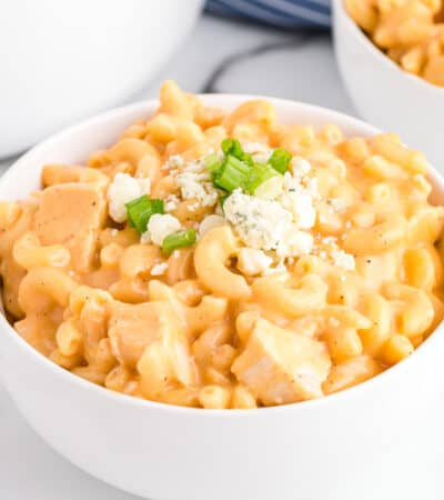 Buffalo Chicken Mac and Cheese in white bowl topped with blue cheese and scallions.
