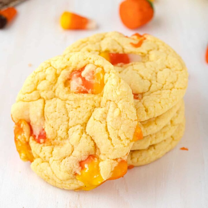 Candy CornCookies stacked on tabletop with one cookie on its side to show candy corn inside them. Extra candy corn are scattered in background.