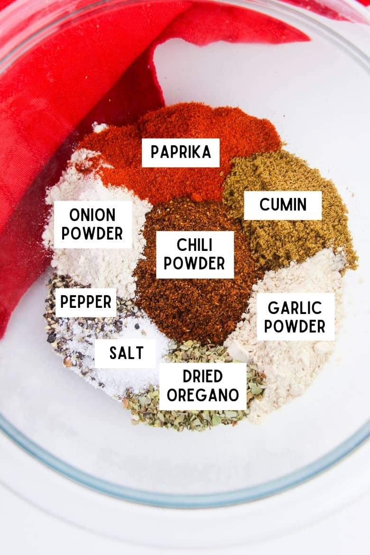 Ingredients for chili seasoning mix in bowl: paprika, cumin, garlic powder, dried oregano, salt, pepper, chili powder, and onion powder.