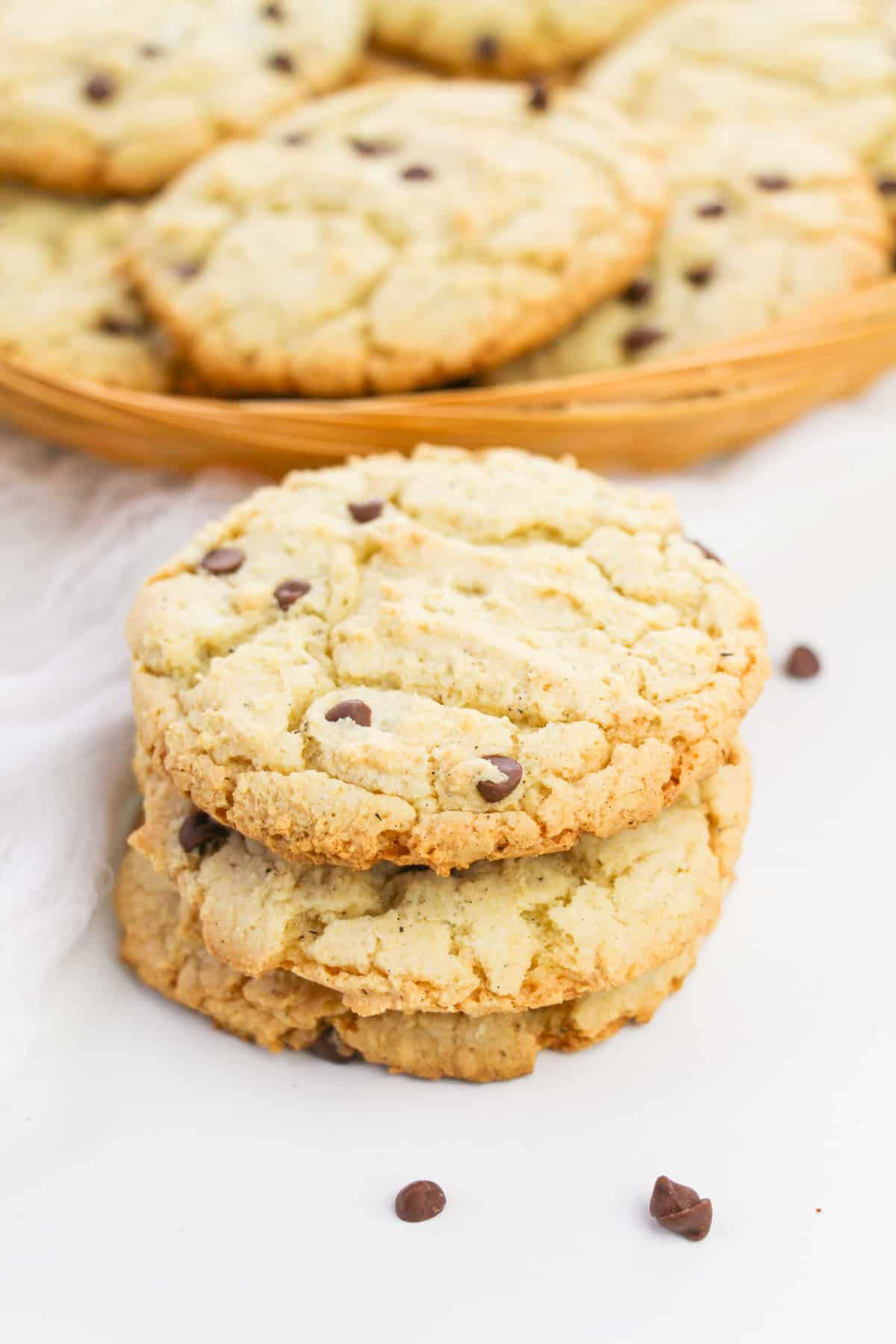 Cake Mix Chocolate Chip Cookies stacked on top of one anther with basket of additional cookies in the background and mini chocolate chips scattered on table