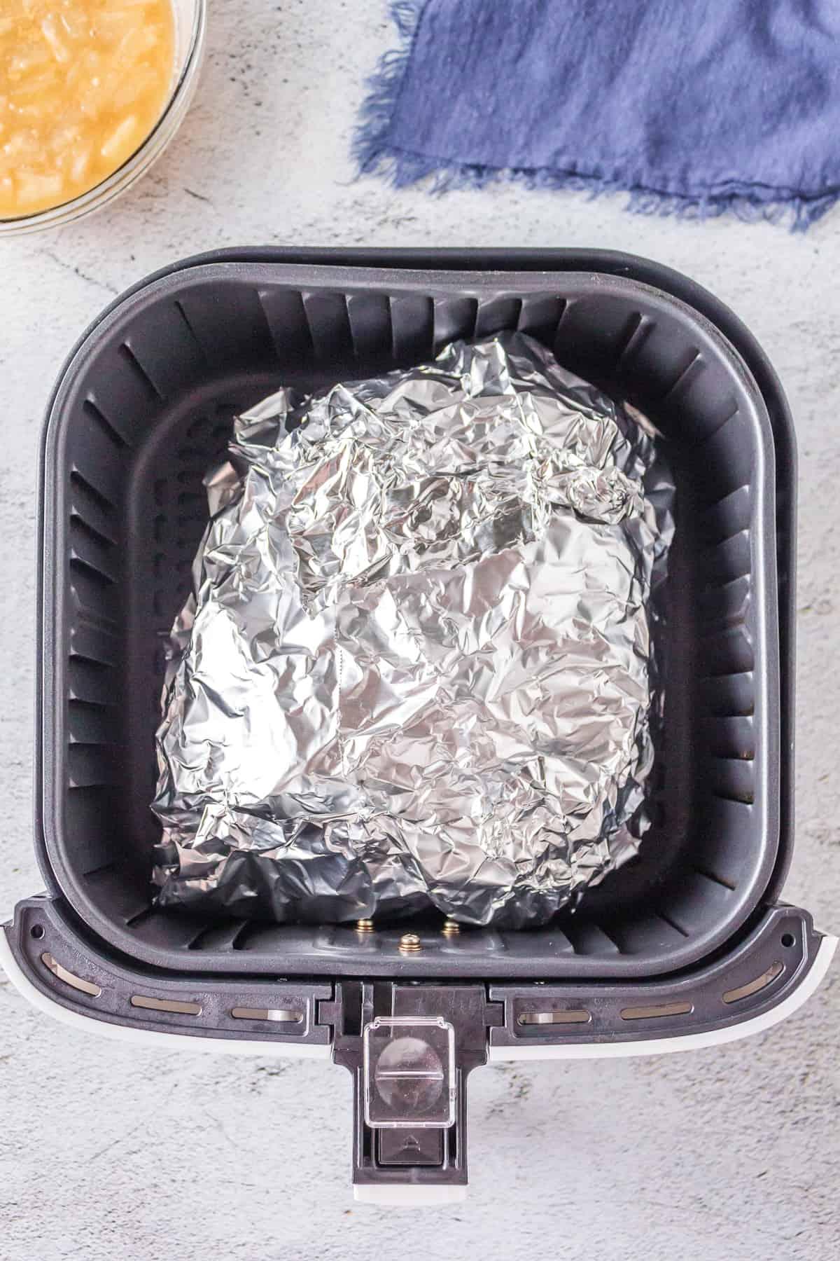 Foil-wrapped ham in air fryer basket