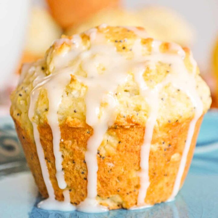 Lemon poppy seed muffin drizzled with lemon glaze which is dripping down the sides