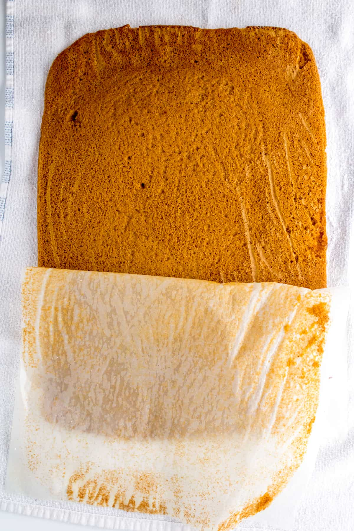 parchment paper being peeled off pumpkin cake