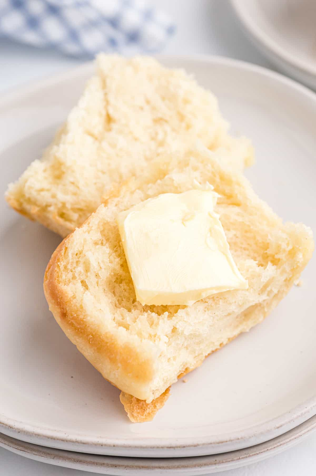 Fluffy potato roll cut in half with a pat of butter on it