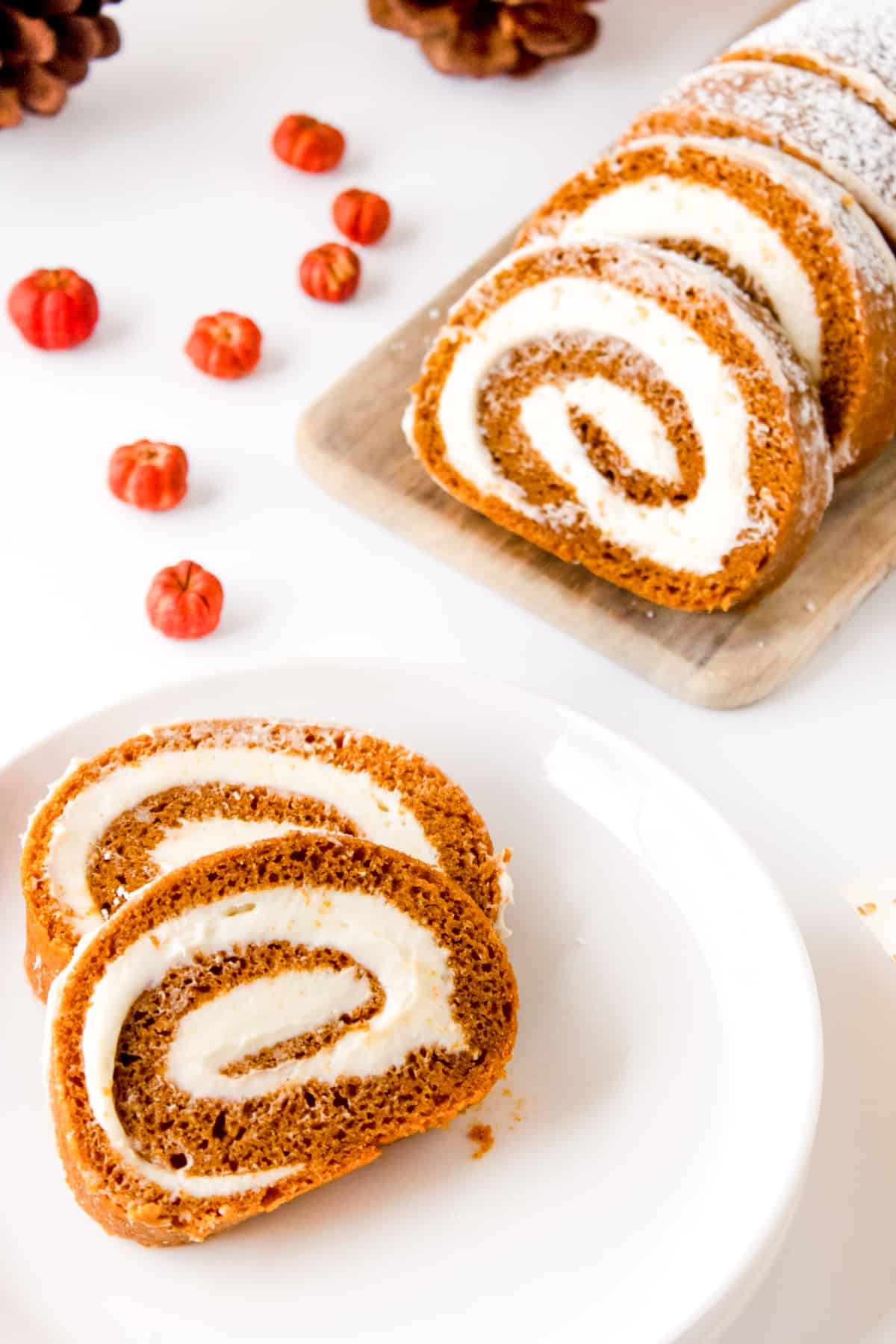 Slices of pumpkin roll cake on white plate with additional slices on light wood board.