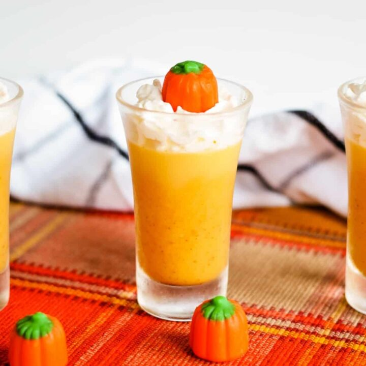 Pumpkin jello shot topped with whipped cream and candy pumpkin