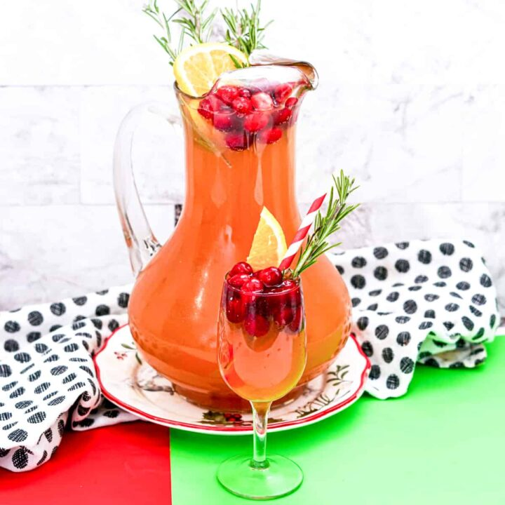 Christmas Punch with vodka and cranberry in a large pitcher garnished with cranberries, orange slice, and rosemary. A glass of the cranberry punch is in front of the pitcher and also garnished with cranberries, orange, and rosemary